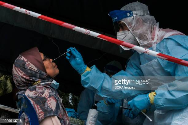 Medical healthcare worker wearing a personal protective equipment takes a nasal swab sample from a senior citizen during the test. Selangor has...