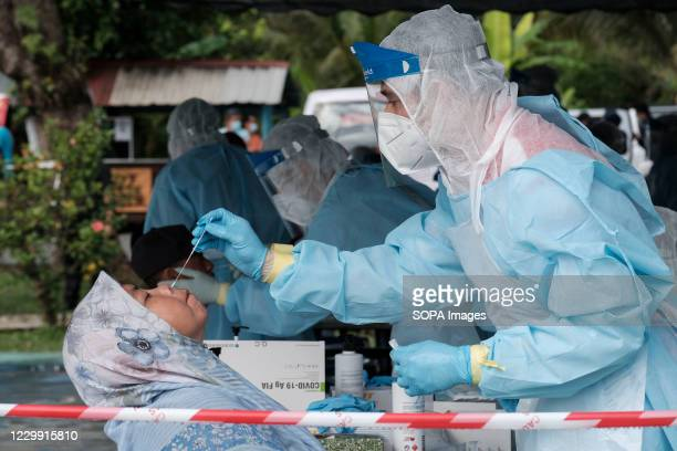 Medical healthcare worker wearing a personal protective equipment takes a nasal swab sample from a resident during the test. Selangor has conducted...