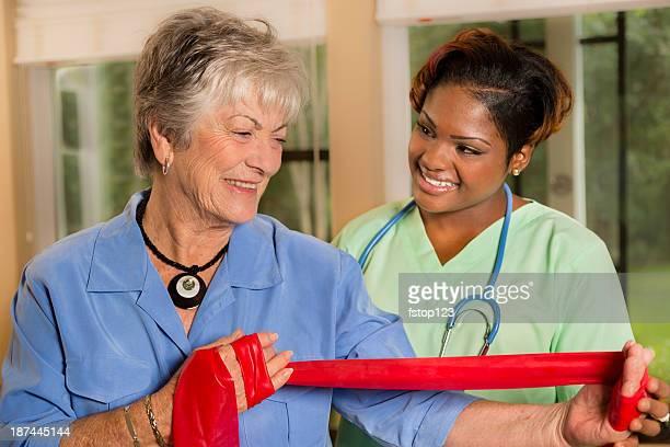 Medizinische: Home healthcare Krankenschwester hilft Frau mit band-Therapie.