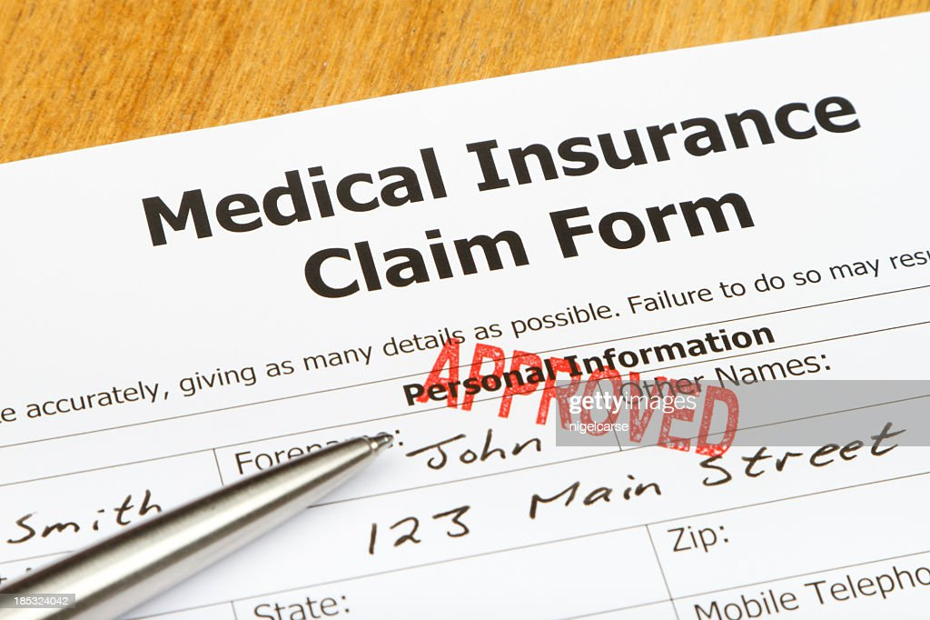 A Medical Insurance Claim Form With A Red Approved Stamp Stock Photo