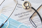 Medical Insurance claim form with stethoscope and surgical face mask.