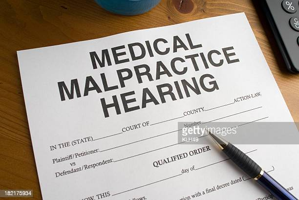 medical malpractice hearing form and pen - medical malpractice stock photos and pictures