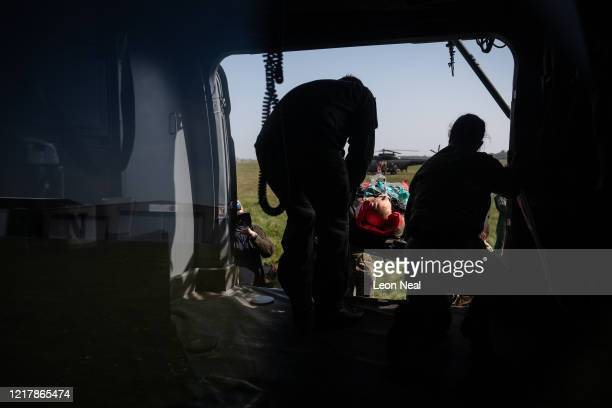 A medical mannequin wearing a ventilator is loaded onto an AgustaWestland AW101 Merlin helicopter as members of the UK Armed Forces work with NHS...