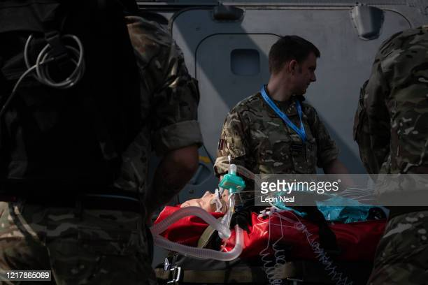 A medical mannequin wearing a ventilator is prepared to be loaded onto an AgustaWestland AW101 Merlin helicopter as members of the UK Armed Forces...
