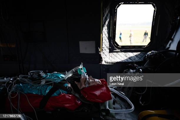 A medical mannequin wearing a ventilator is seen onboard an AgustaWestland AW101 Merlin helicopter as members of the UK Armed Forces work with NHS...