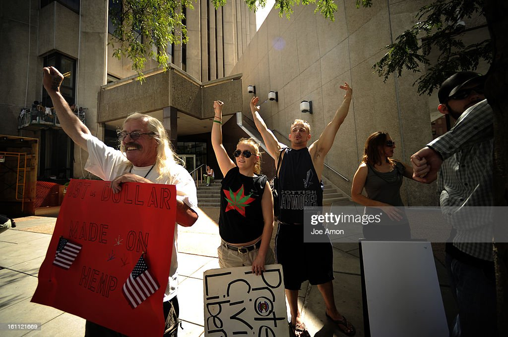 Medical marijuana activist's 'Wayward' Bill Chengelis, Lauren Laire and passerby Jason Linam react to supporting beeps from cars in front of Wells Fargo as they march in downtown Denver to protest banks in the area closing the accounts with local medical  : News Photo