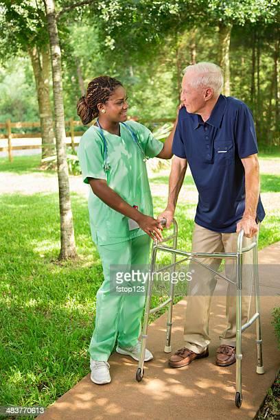 Medical:  Nurse talking with senior man using walker.
