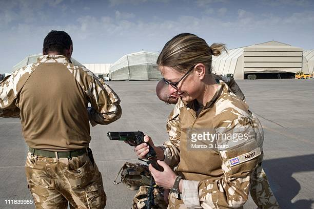 Medical Officer MAJ Clare Hayes-Bradley, 35-years-old from the Lister Hospital in Stevenage checks her pistol at the flight line in Camp Bastion on...