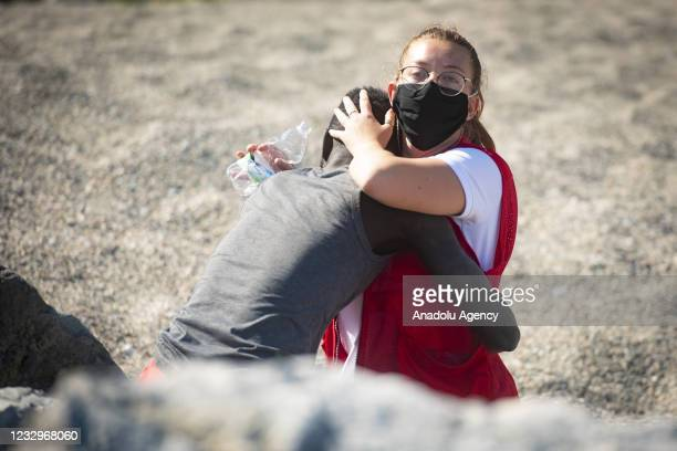Medical official trying to taking care of a migrant at the area in Ceuta on May 18, 2021. Migrants arrived swimming to Spanish territory of Ceuta....