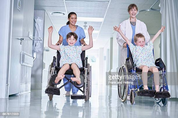 Medical orderlies having fun pushing boy patients in wheelchair on hospital childrens ward