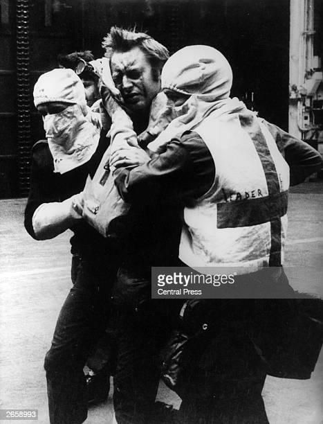 Medical orderlies wearing antiflash gear tend a wounded survivor of HMS Sheffield aboard HMS Hermes during the Falklands War