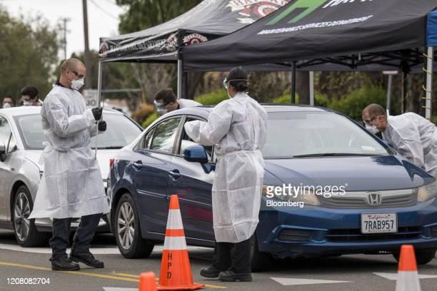 Medical personal check the temperature of people at a free Covid19 testing site in Hayward California US on Monday March 23 2020 Governor Newsom on...