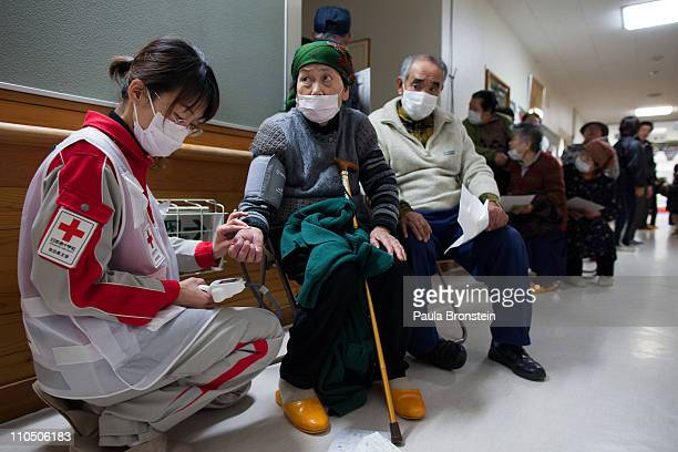 Medical personal from the Japanese Red Cross treats earthquake victims at a medical clinic at an evacuation center where hundreds of homeless are...