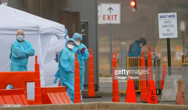 Medical personnel at Advocate Lutheran General Hospital in Park Ridge, Ill. Wait for patients as they conduct drive-thru COVID-19 testing on March...