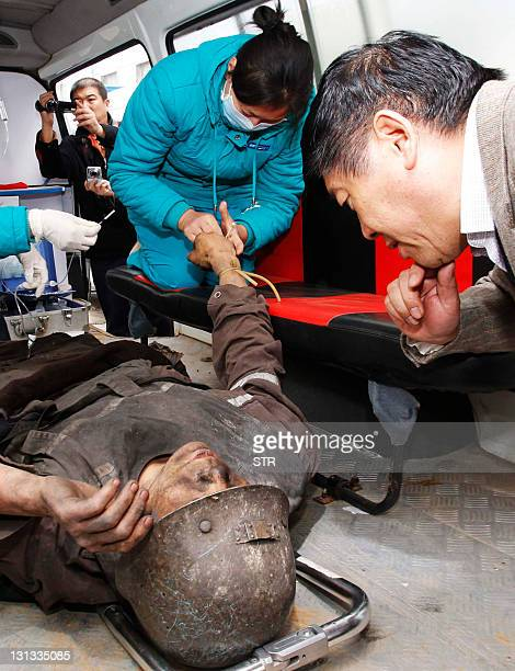 Medical personnel attend to a survival coal miner who was rescued after a rock blast occurred in a mine shaft at the Henan Yima Coal Mine Group's...