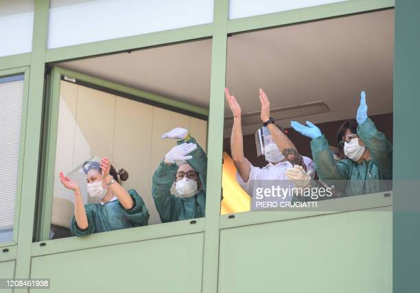 Medical personnel cheers from the windows of the Honegger nursing home where 35 people have died so far from coronavirus in Albino, Italy on March 28...