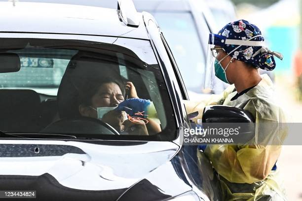 """Medical personnel conduct Covid-19 testing at a """"drive-through"""" site in Miami, on August 3, 2021. - In Florida cars are lining up for Covid-19..."""