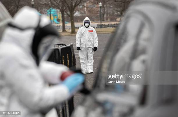 Medical personnel dressed in personal protective equipment prepare to give a coronavirus swab test at a drivethru testing station at Cummings Park on...