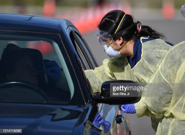 Medical personnel from Riverside University Health Systems hospitals administer a Coronavirus Test to an individual during drivethrough testing in...