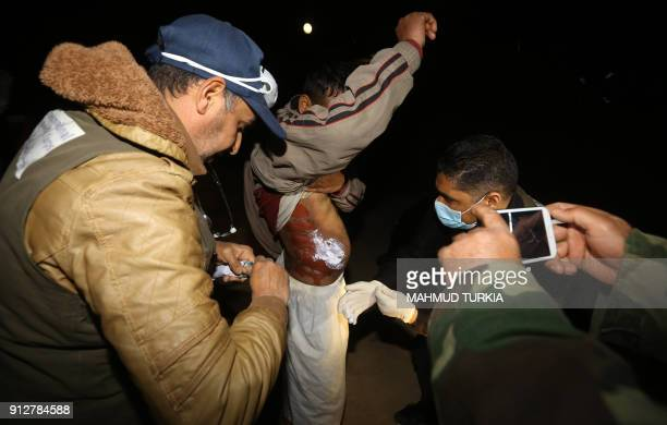 TOPSHOT Medical personnel give medical aid to a migrant upon arrival at a naval base in Tripoli late on January 31 after migrants were rescued off...