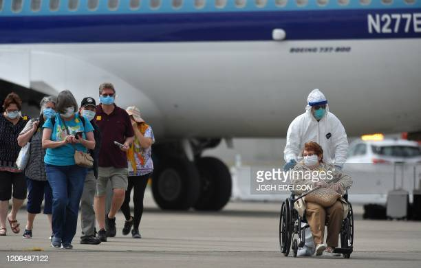 Medical personnel help load passengers from the Grand Princess cruise ship onto airplanes at Oakland International Airport in Oakland California on...