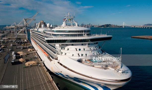 Medical personnel help load passengers onto buses as they are disembarked from the Grand Princess cruise ship at the Port of Oakland in Oakland...