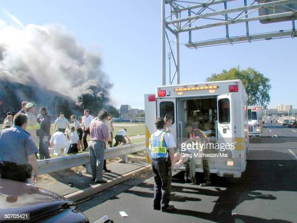 Medical personnel loading the wounded into an ambulance at the first medical triage area set up outside the Pentagon after terrorists hijacked a...