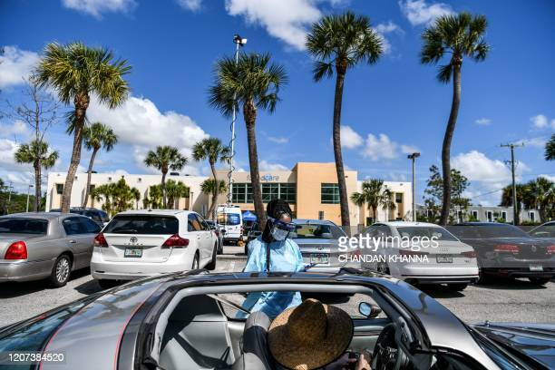 A medical personnel member stands near Juan Parra's car as she fills out a questionnaire at a drivethru coronavirus testing lab set up by a local...