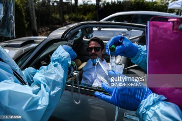 A medical personnel member takes samples of of Juan Parra at a drivethru coronavirus testing lab set up by a local community center in West Palm...
