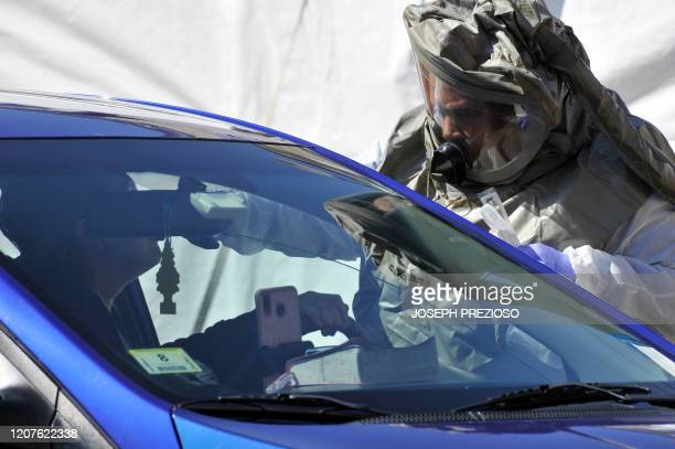 A medical personnel member takes samples of person at a drivethru coronavirus testing lab set up at Somerville Hospital in Somerville Massachusetts...