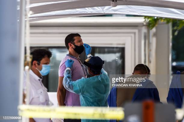 A medical personnel member takes samples on a man at a walkin and drivethrough coronavirus testing site in Miami Beach Florida on June 24 2020 With...