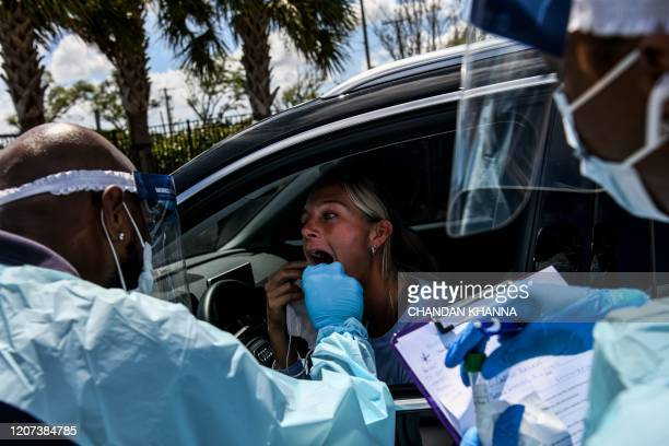 TOPSHOT A medical personnel member takes samples on a woman at a drivethru coronavirus testing lab set up by a local community center in West Palm...