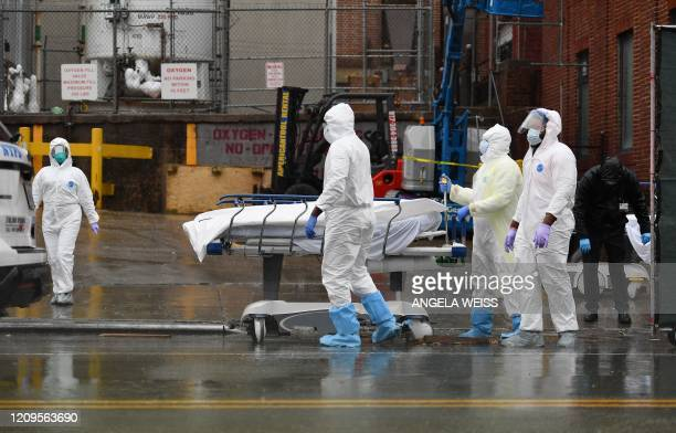Medical personnel move a deceased patient to a refrigerated truck serving as make shift morgues at Brooklyn Hospital Center on April 09 2020 in New...