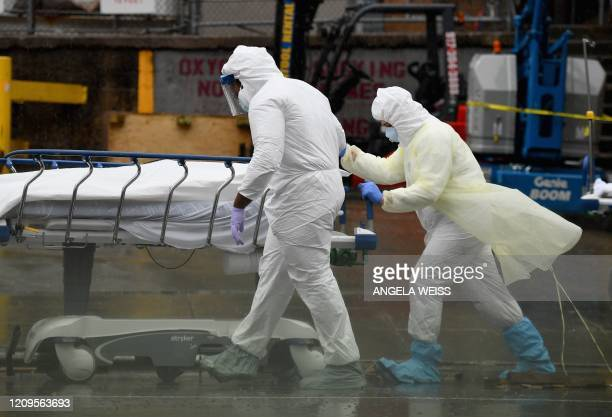 TOPSHOT Medical personnel move a deceased patient to a refrigerated truck serving as make shift morgues at Brooklyn Hospital Center on April 09 2020...
