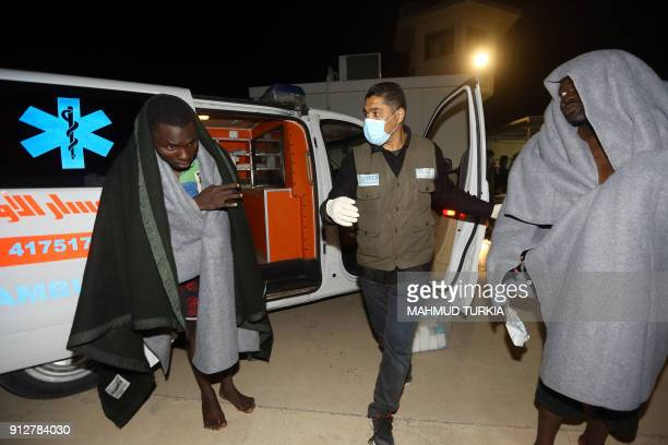 Medical personnel of UN Refugee Agency UNHCR take care of migrants at a naval base in Tripoli late on January 31 after migrants were rescued off...