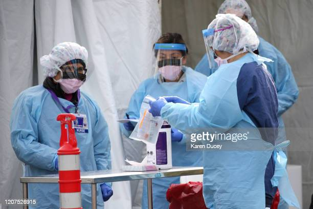 Medical personnel process a sample taken from a patient during a COVID19 screening at an appointmentonly driveup clinic set up by the University of...