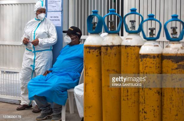 Medical personnel remain near oxygen cylinders at the entrance door of the COVID-19 area of the Moscoso Puello Hospital in Santo Domingo on August...