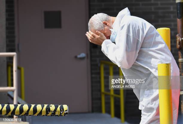 A medical personnel rubs his face outside the Wyckoff Heights Medical Center on April 07 2020 in Brooklyn New York