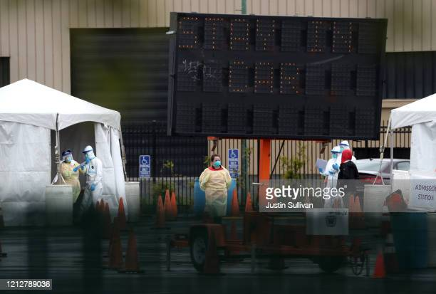 Medical personnel set up a coronavirus drivethru test clinic at the San Mateo County Event Center on March 16 2020 in San Mateo California Drivethru...