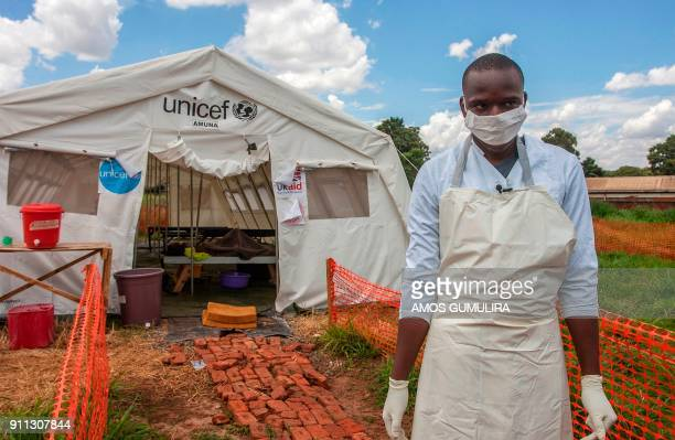 TOPSHOT A medical personnel stands in front of a ward of a Cholera Treatment Centre funded by the Unicef Malawi Red Cross and UK Aid at Bwaila...