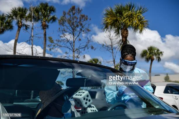 """Medical personnel stands near a woman's car as she fills up the questionnaire at a """"drive-thru"""" coronavirus testing lab set up by the local community..."""
