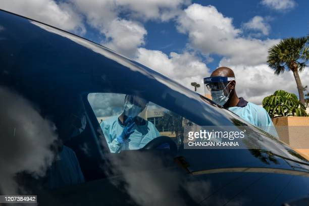 """Medical personnel stands near a woman's car as she fills up the questionnaire at a """"drive-thru"""" coronavirus testing lab set up by local community..."""
