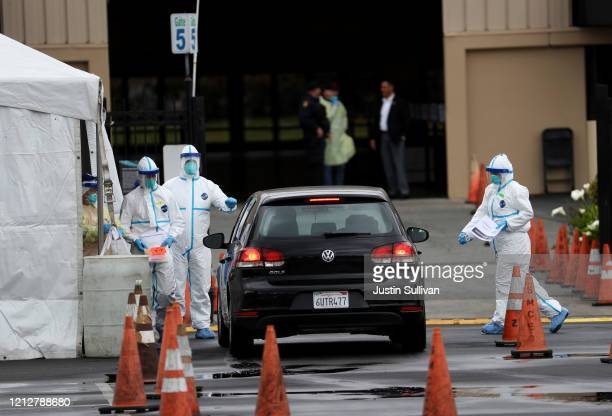 Medical personnel surround a car that is going through a coronavirus drive-thru test clinic at the San Mateo County Event Center on March 16, 2020 in...