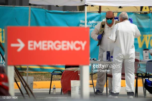 Medical personnel talk at a drive-thru Coronavirus COVID-19 testing station at West Jefferson Medical Centeron March 17, 2020 in New Orleans,...