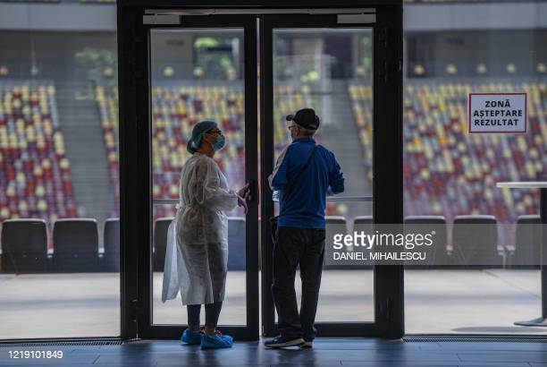 Medical personnel talks with a man waiting for the results for Coronavirus test at National Arena stadium in Bucharest June 10, 2020. - A testing...