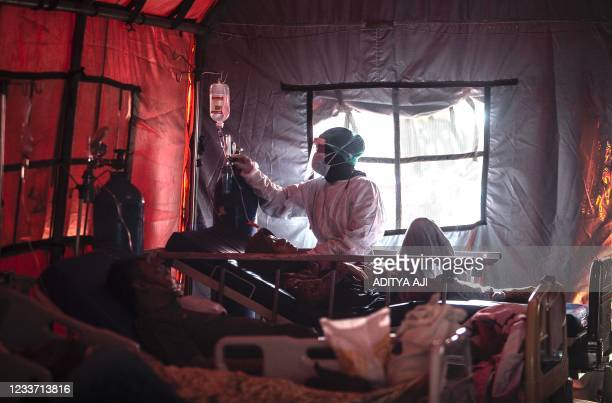 Medical personnel tend to Covid-19 patients in a tent set up outside a hospital in Bogor on June 29 as infections soar in Indonesia.