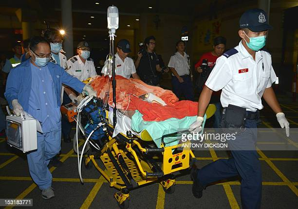 Medical personnel transfer a victim from an ambulance at a hospital after at least 30 people were injured in a collision between a ferry and another...