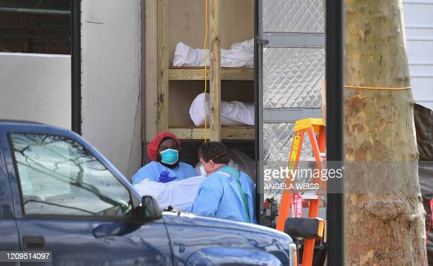 Medical personnel transport a deceased patient from a refrigerated truck to Kingsbrook Jewish Medical Center on April 8, 2020 in Brooklyn, New York....