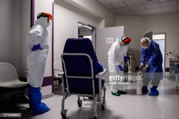 Medical personnel wear protective suits, masks, gloves and face shields as they administrate oxygen to a possible COVID 19 patient during their shift...