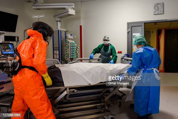 Medical personnel wear protective suits, masks, gloves and face shields as they transfer the body of a deceased COVID-19 patient to a metal coffin at...